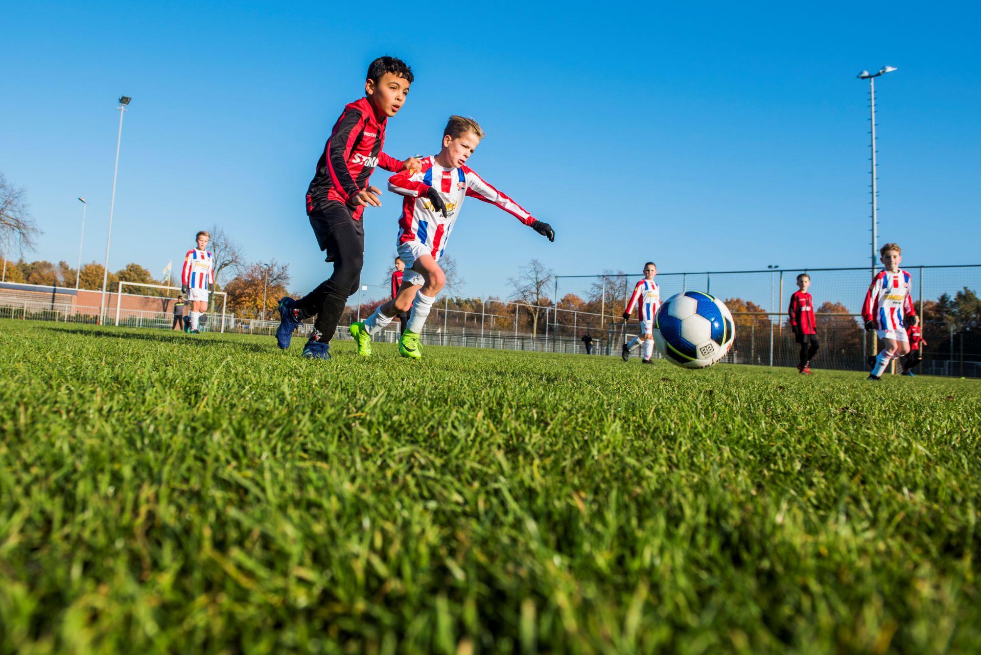 Actiefoto van voetbalwedstrijd kinderen Helmondia-Mulo JO10-1 - Stiphout JO10-1