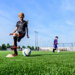 Meisje voetbalt op kunstgrasveld