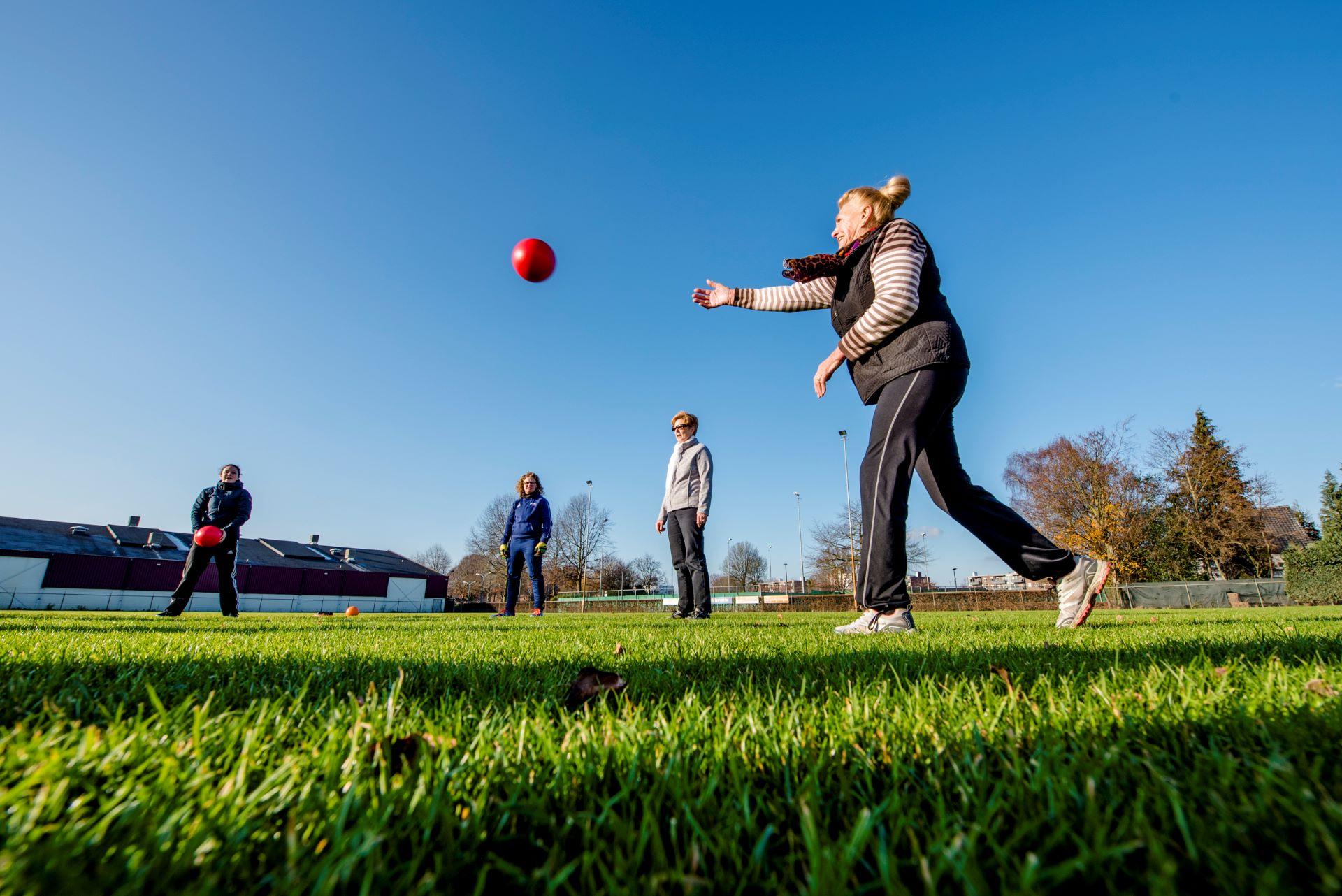 Senioren gooien met bal tijdens JIBB Golden Sports bij korfbalvereniging OEC