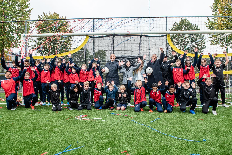Groepsfoto van voetballertjes met wethouder Harrie van Dijk in goal