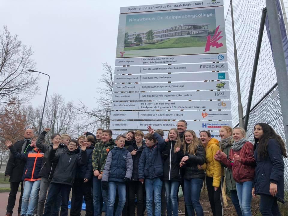 Leerlingen van het Knippenbergcollege bij het bouwbord dat onthuld is bij de start van de bouwwerkzaamheden