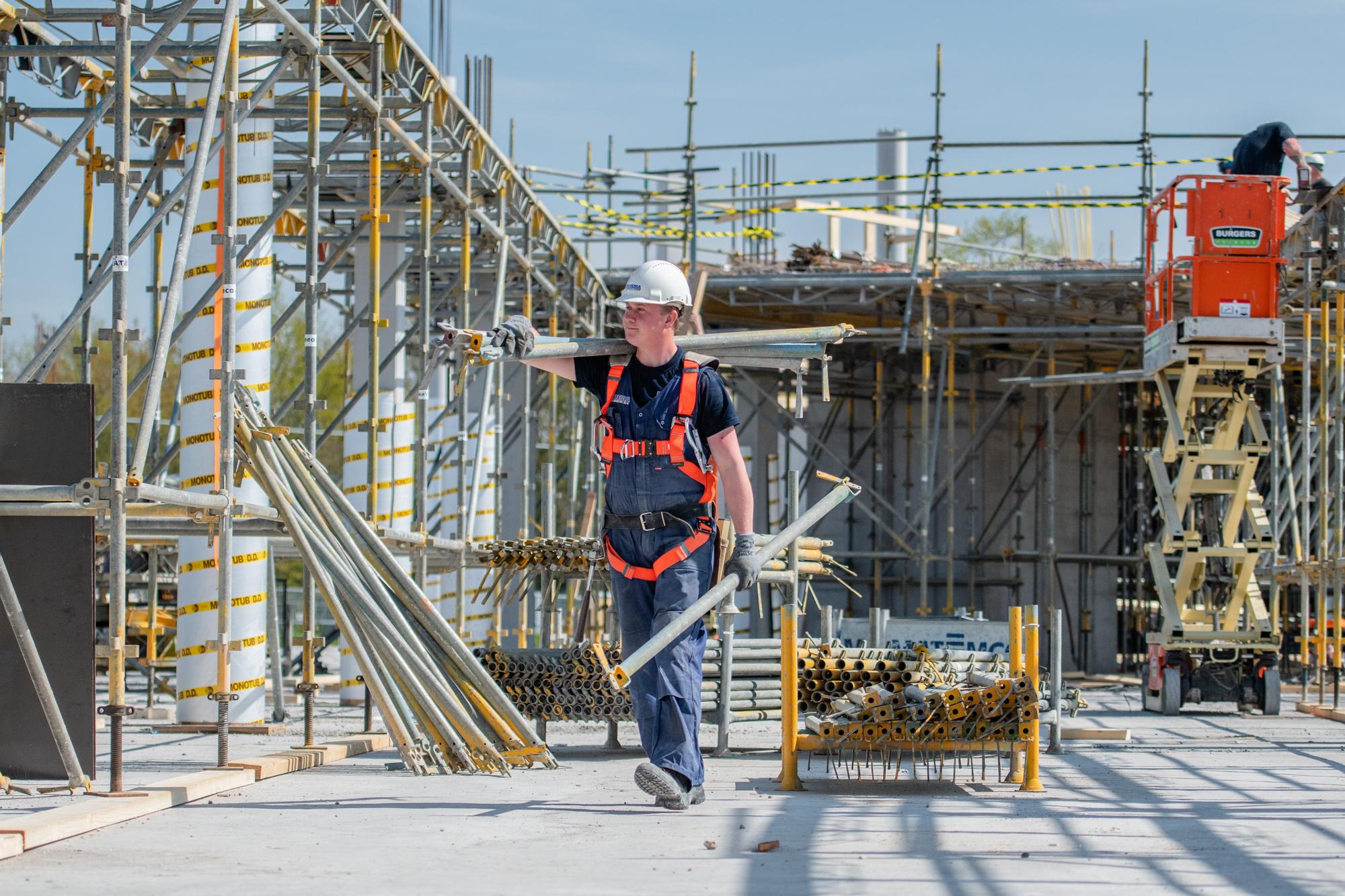 Een bouwvakker loopt op de bouwplaats met steigerbuizen