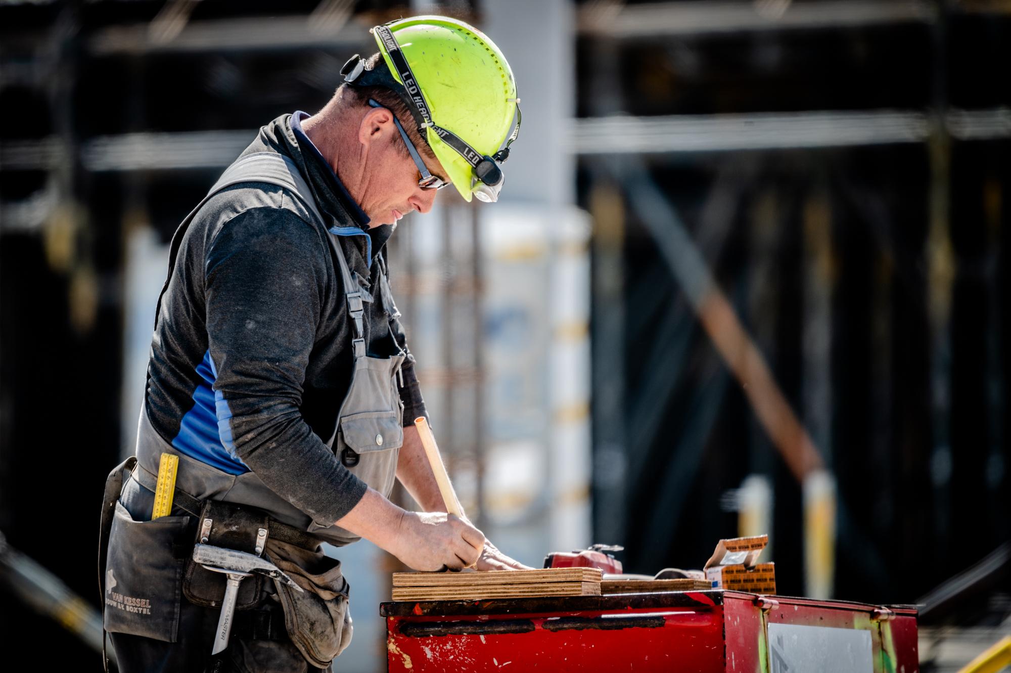 Een bouwvakker meet iets op tijdens de bouw van het Knippenbergcollege