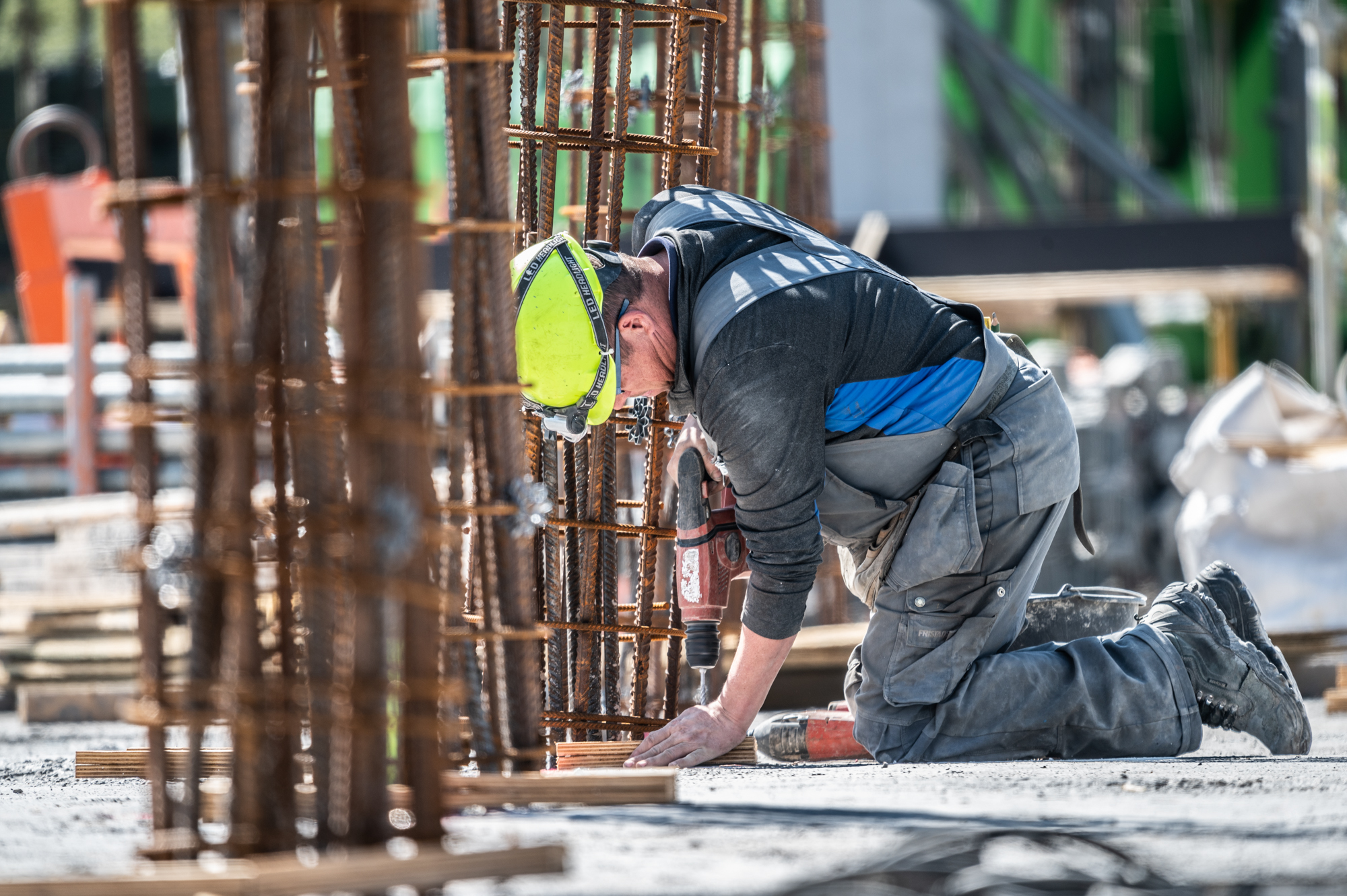 Een bouwvakker aan het werk op de bouwplaats van het Knippenbergcollegge