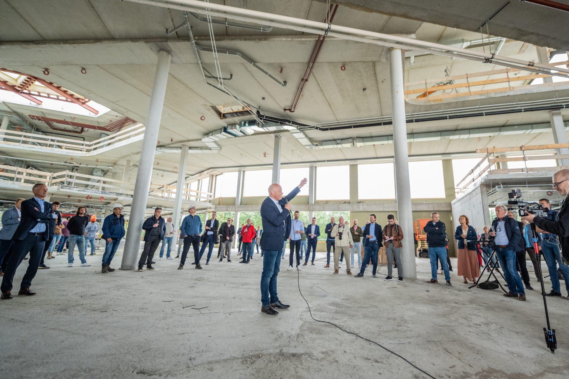 Wethouder Harrie van Dijk brengt een toast uit in schoolgebouw in aanbouw